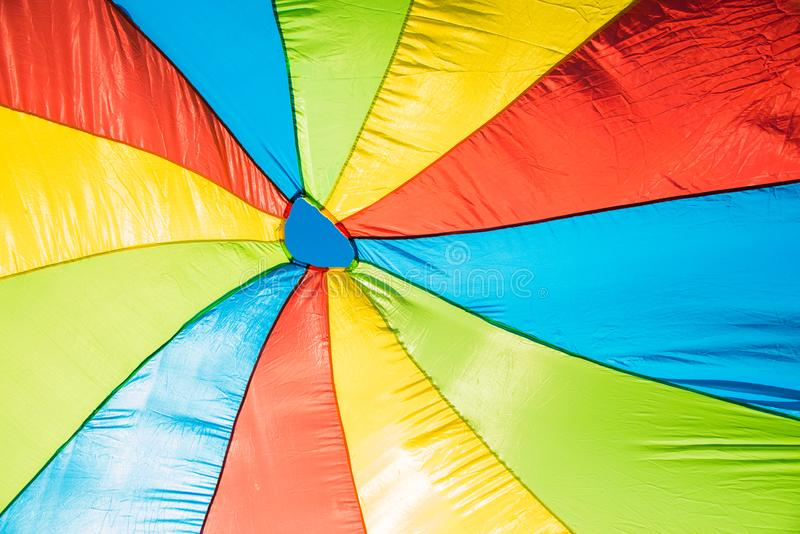 A parachute in many colors. A parachute in many different bright colors and a little bit of sky royalty free stock images