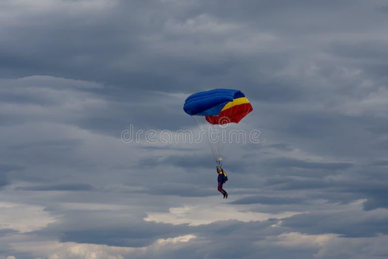 Parachuter, das für die Landung sich vorbereitet lizenzfreie stockbilder