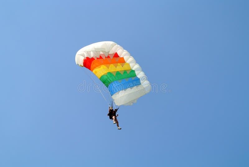 Parachuter, das mit buntem Fallschirm in den Regenbogenfarben auf Fallschirmspringenschale im freien Fall springt lizenzfreies stockfoto