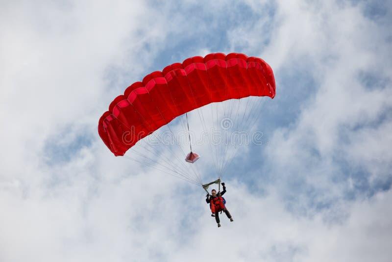 Parachuter, das mit einem roten Fallschirm absteigt lizenzfreies stockbild