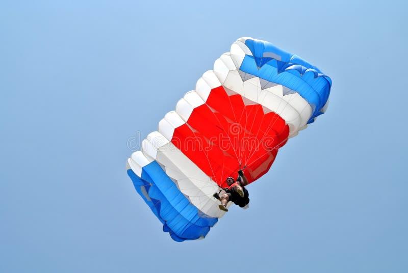 Parachuter mit blauem weißem rotem Fallschirm stockfoto