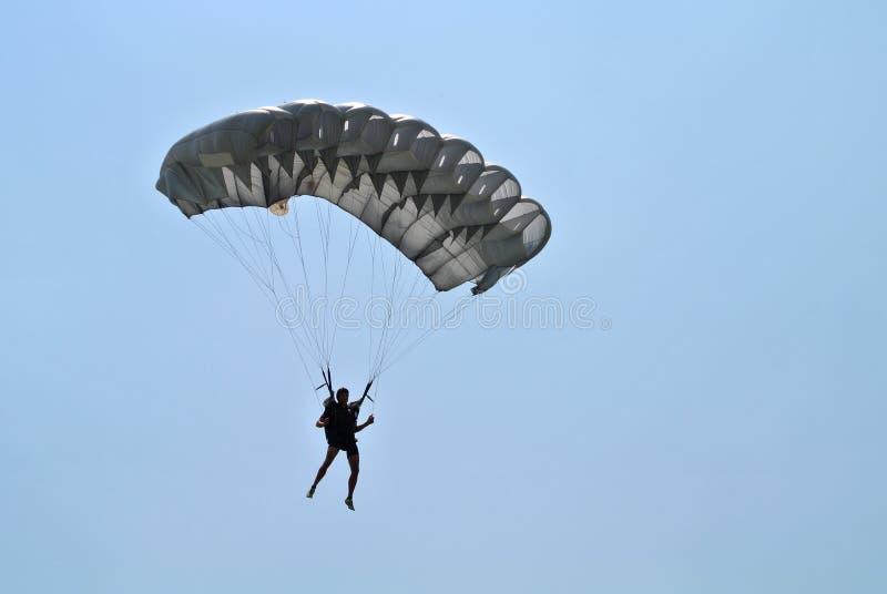 Parachuter mit dem grauen Fallschirmim freien fall springen lizenzfreies stockfoto
