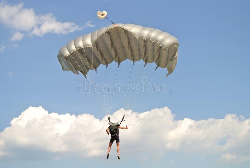 Parachuter mit grauem Fallschirm auf der Fallschirmspringenschale gesehen von der Rückseite lizenzfreie stockbilder