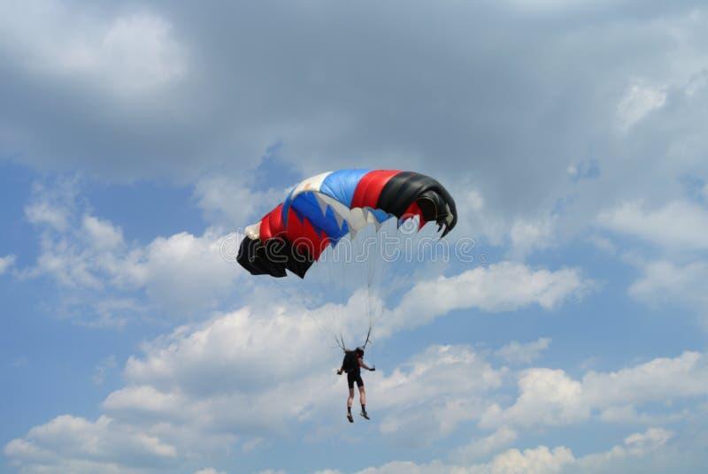 Parachuter mit schwarzem rotem blauem weißem Fallschirm auf Fallschirmspringenschale von der Rückseite lizenzfreies stockbild