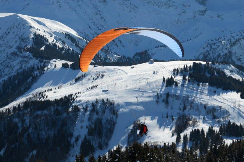 Parachuter sobre la cuesta nevosa en las montañas fotografía de archivo