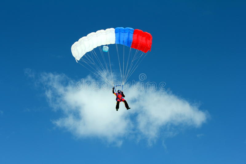 Parachuting. Freefall in blue sky royalty free stock image