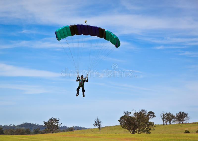 Parachuting. Skydiver parachuting down to the ground royalty free stock images