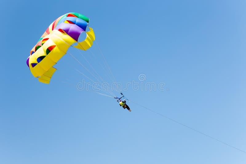 Parachuting above the sea, skydiver. Summer vacation royalty free stock image