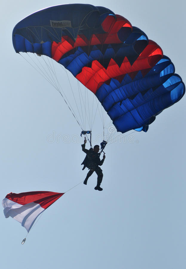 Parachuting attraction to celebrate Indonesian Independence Day. Indonesians military personel performs a parachuting attraction during ceremony to mark the stock photos