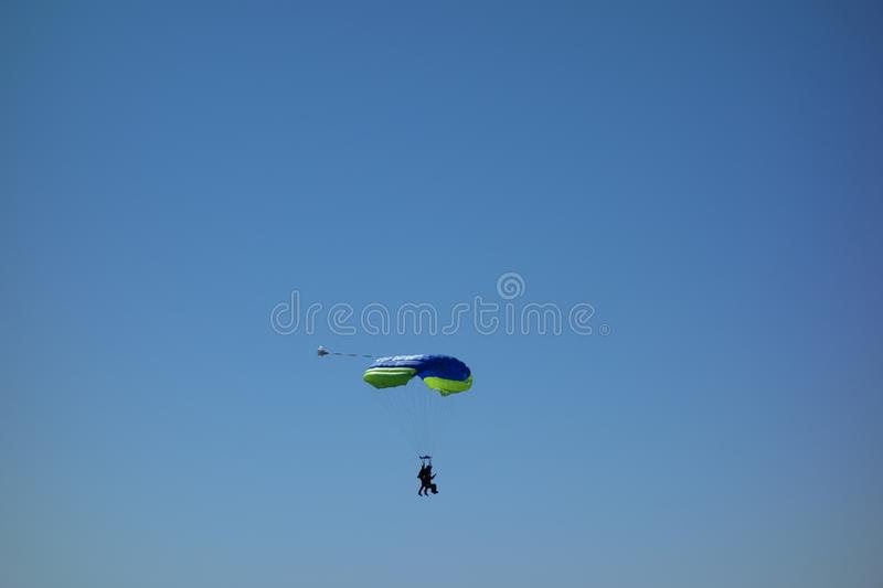 Parachuting in tandem. Descent to landing. Tandem parachuting. A pair of parachutists in descent to landing against a clear blue sky stock photo