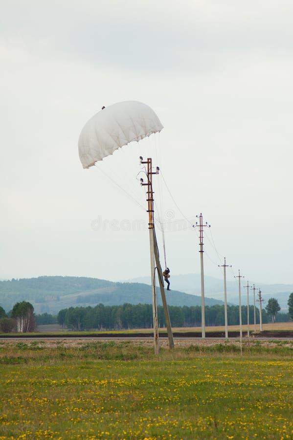 Parachutist посадки на линии электропередач стоковое фото rf