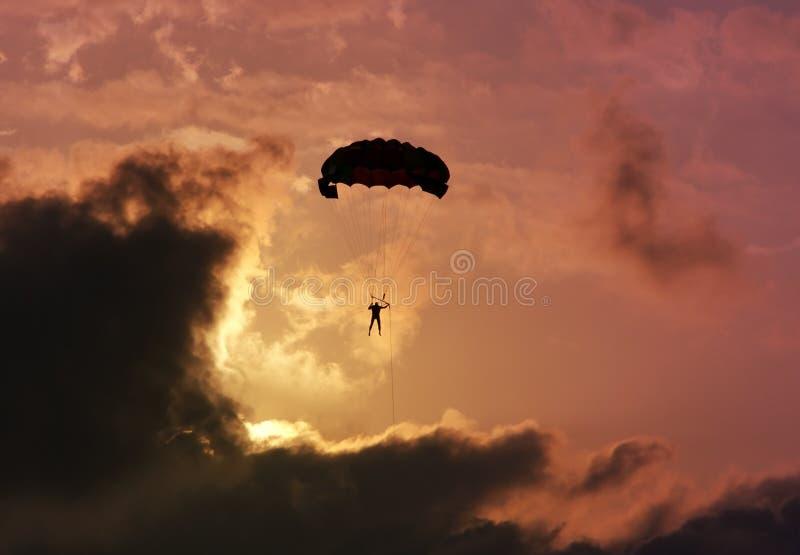 Parachutist gegen einen bunten Sonnenuntergang und Wolken. stockfotografie