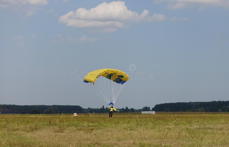 A parachutist on a guided parachute lands on the field royalty free stock photos