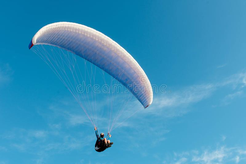 Parachutist soaring in a beautiful blue sky with light clouds stock photography