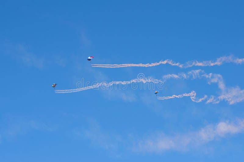 Parachutists летания в небе на авиасалоне редакционо стоковая фотография rf