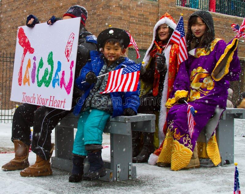 Parada chinesa do ano novo com a bandeira de ondulação da criança foto de stock