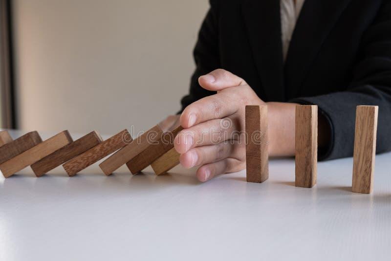 A parada da mão da mulher obstrui a madeira para para proteger o outro, o risco do conceito de gestão e o plano da estratégia foto de stock royalty free