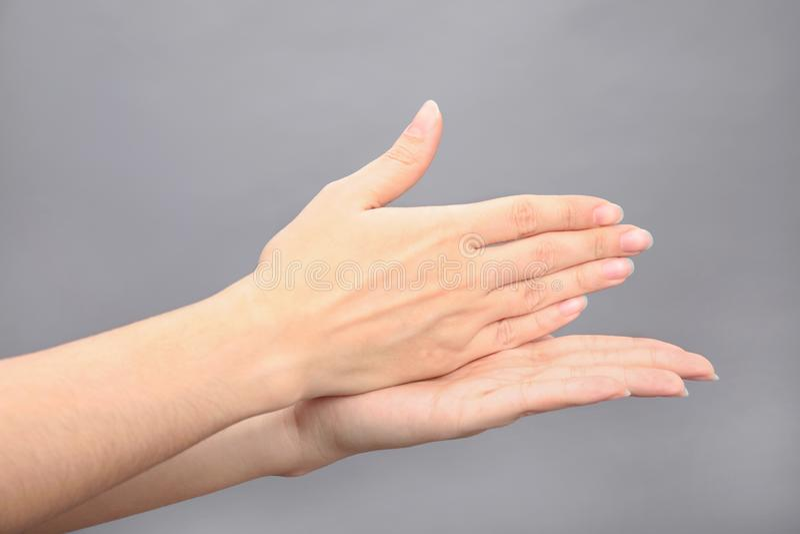 Parada da palavra da exibição da mulher no fundo cinzento Linguagem gestual fotos de stock