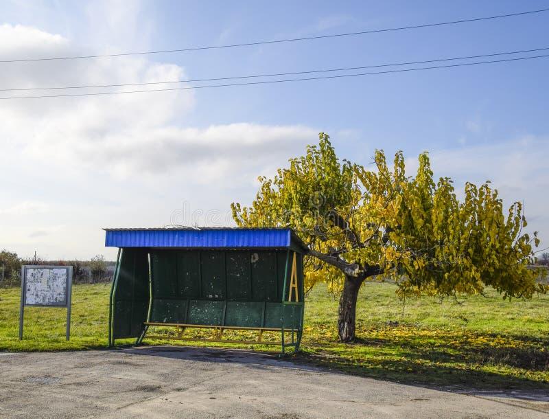 Parada de autobús en el pueblo El tapón al lado del árbol imagen de archivo libre de regalías