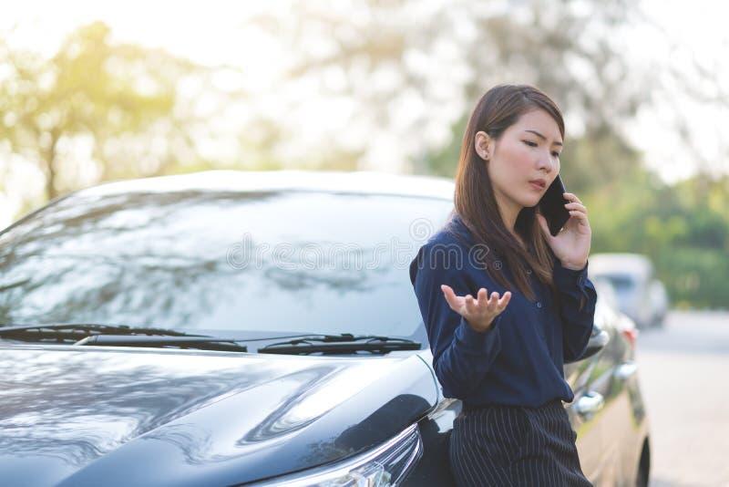 Parada de la empresaria un coche y el hablar en el teléfono para su busi foto de archivo libre de regalías