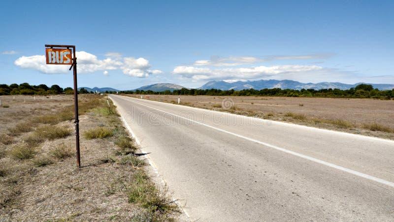 Parada de omnibus en un camino vacío fotografía de archivo