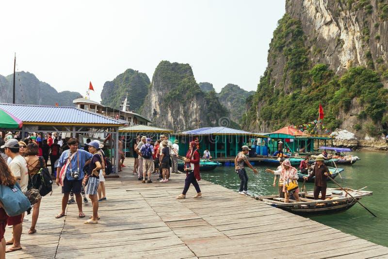 Parada del barco con muchos turistas que esperan viajar dentro de la cueva de la piedra caliza con la isla de la piedra caliza en imagen de archivo