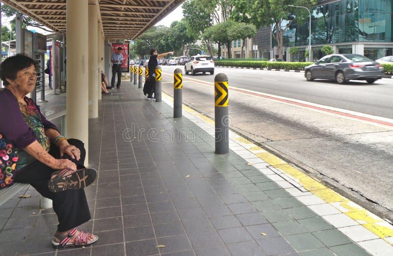 Parada do ônibus em Bugis com os povos que esperam um passeio em Singapura do centro imagens de stock
