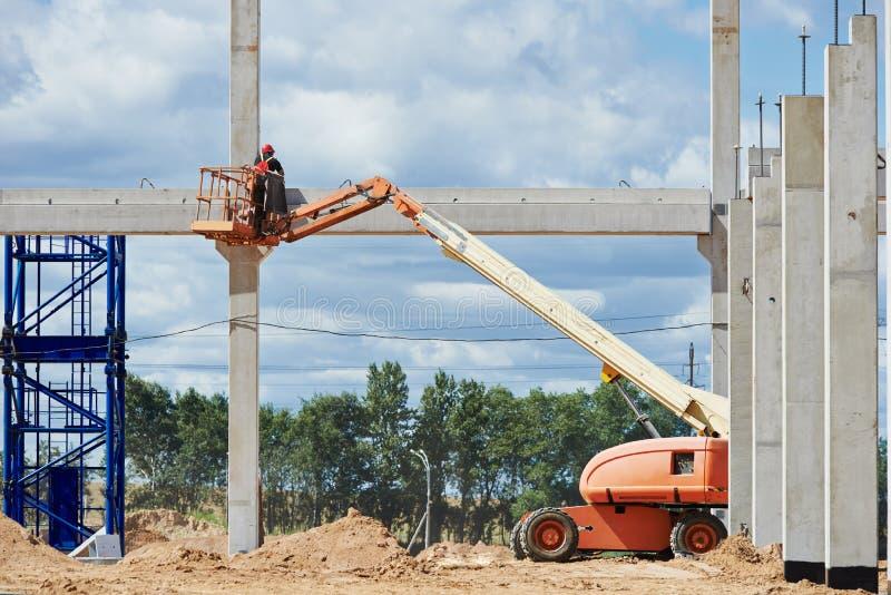 Parada do trabalhador do construtor acima do polo concreto imagem de stock