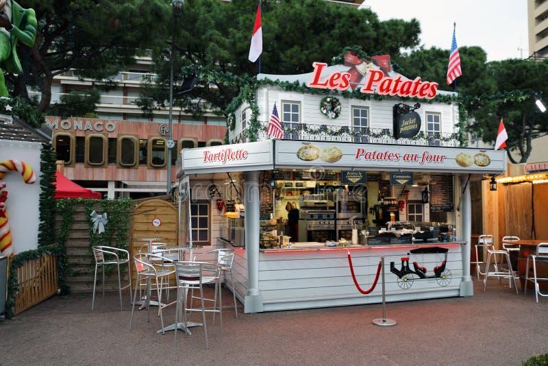 Parada justa iluminada del mercado del quiosco de la Navidad que vende las patatas calientes de la comida francesa tradicional imágenes de archivo libres de regalías