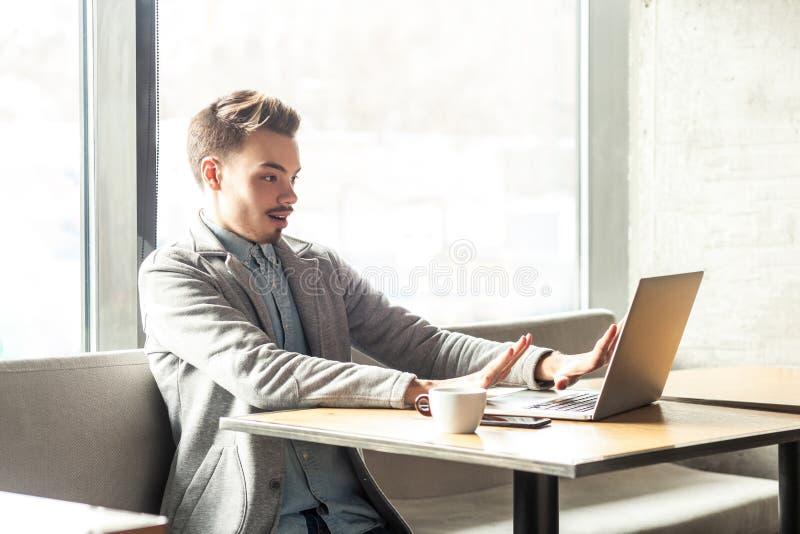 Parada! O retrato da vista lateral do homem de negócios novo assustado emocional no blazer cinzento está sentando-se no café e es imagem de stock