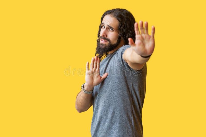 parada Retrato del hombre joven barbudo asustado o confuso con el pelo rizado largo en la situación gris de la camiseta con gesto imagen de archivo libre de regalías