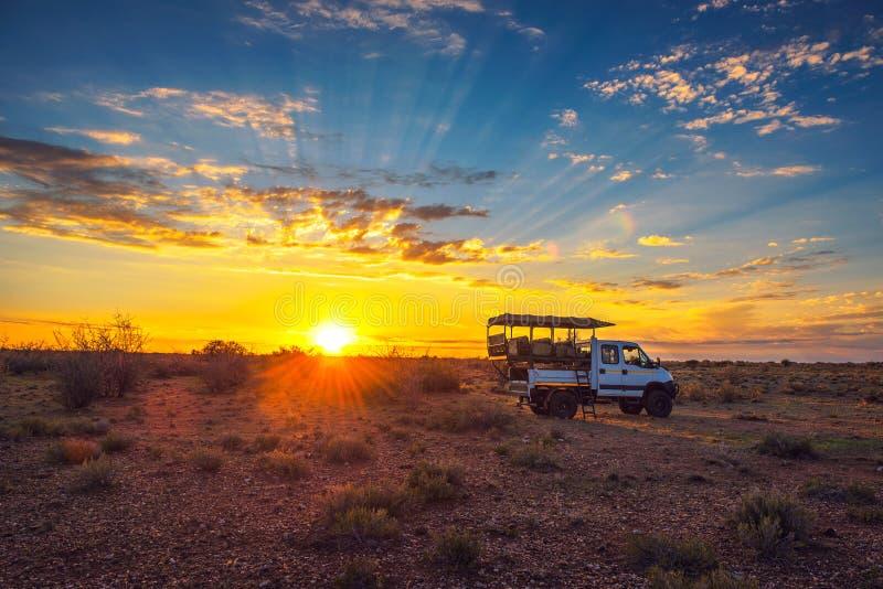 Paradas africanas del vehículo del safari en el desierto de Kalahari para la puesta del sol dramática imágenes de archivo libres de regalías