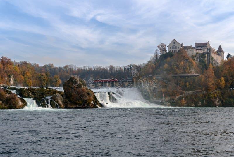 Paradas rojas de un tren de la flecha encima del puente en Rhine Falls para ver el paisaje maravilloso de la cascada y el castill imagenes de archivo
