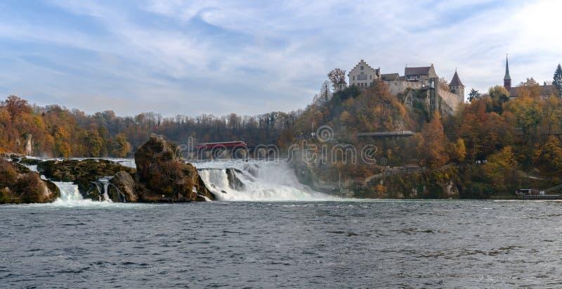 Paradas vermelhas de um trem da seta sobre a ponte em Rhine Falls para ver dentro a paisagem maravilhosa da cachoeira e o castelo imagens de stock