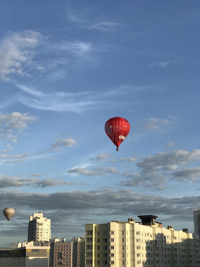 Parade of balloons over the city. Aerostats of different colors fly in the blue sky above the houses. MINSK, MINSKAYA, BELARUS, AUGUST 26, 2017; Parade of stock photos