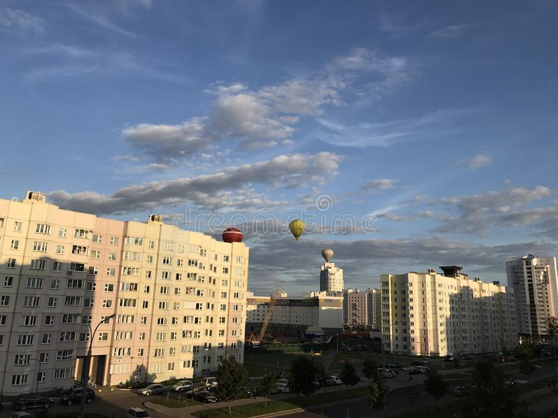 Parade of balloons over the city. Aerostats of different colors fly in the blue sky above the houses. MINSK, MINSKAYA, BELARUS, AUGUST 26, 2017; Parade of stock image