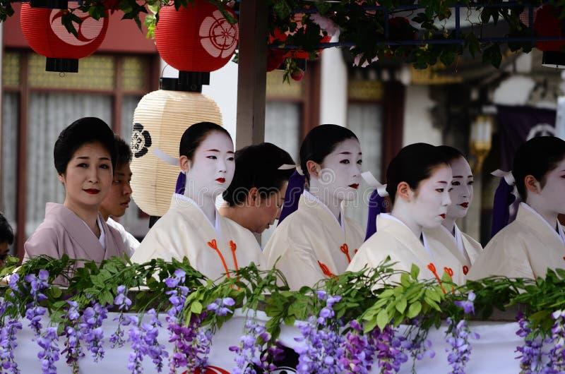 Parade of flowery Geisha girls at Gion festival. Geisha girls riding on the flowery float of Gion Matsuri festival, Kyoto Japan stock image