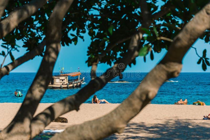 Paradies-Insel-Strand Leute nehmen auf dem Sand ein Sonnenbad Boot im Meer auf den Wellen Tropischer Baum im Vordergrund stockfotos