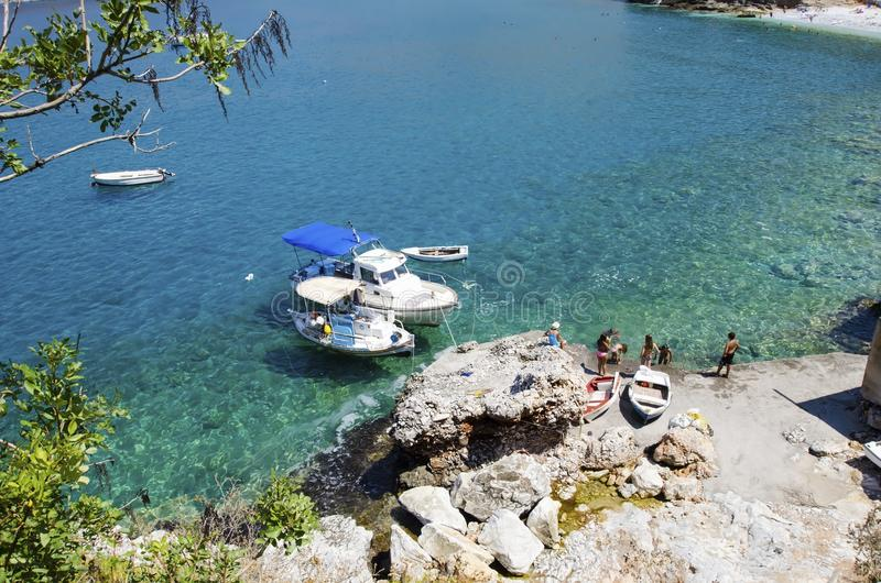 Paradise beach. Two boats embarked and people swimming by the shore near Diros caves in Greece stock photography