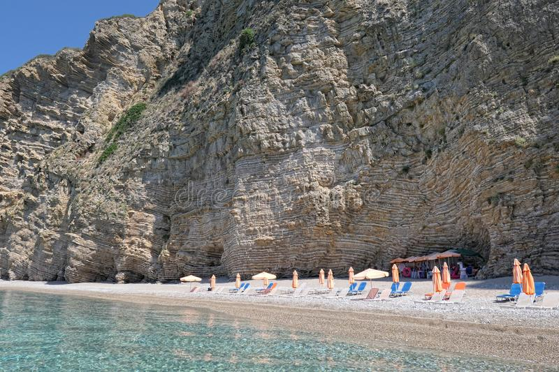paradise beach part names Chomi Beach of Liapades at Corfu Island (Greece). Sedimentary rock cliff of chalk rocks, sun chairs and royalty free stock photography