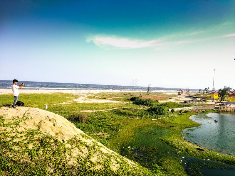 Paradise beach and Sand beach. A tourist is taking pictures of the beauty of the Sand beach located at Pondycherry/puducherry Ind royalty free stock photo