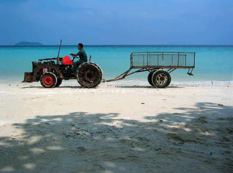 Paradise Beach Thailand Worker. The noise of a rusty tractor driven by one of the hotel employees, breaks the morning silence in Laem Ton beach in Koh Phi Phi royalty free stock images
