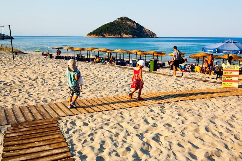 Paradise Beach, Thassos, Greece. Tourists on boardwalk on sandy Paradise Beach in Thassos, Greece on sunny day royalty free stock photo