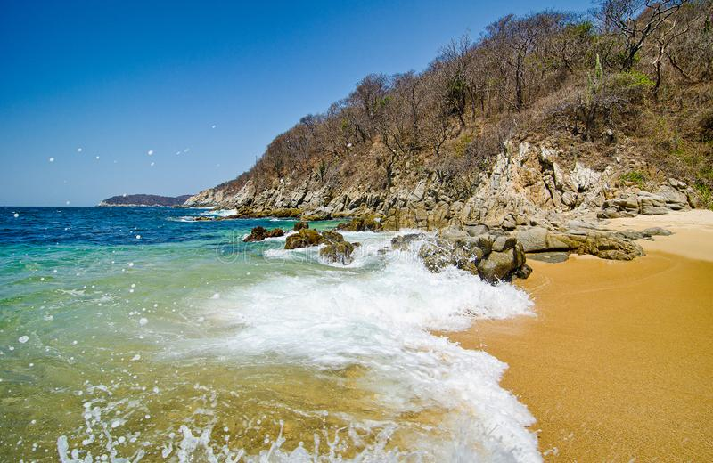 Paradise sand beach with turquoise blue water in Huatulco, Oaxaca, Mexico.  royalty free stock image