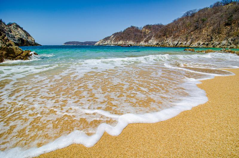Paradise sand beach with turquoise blue water in Huatulco, Oaxaca, Mexico.  royalty free stock photos