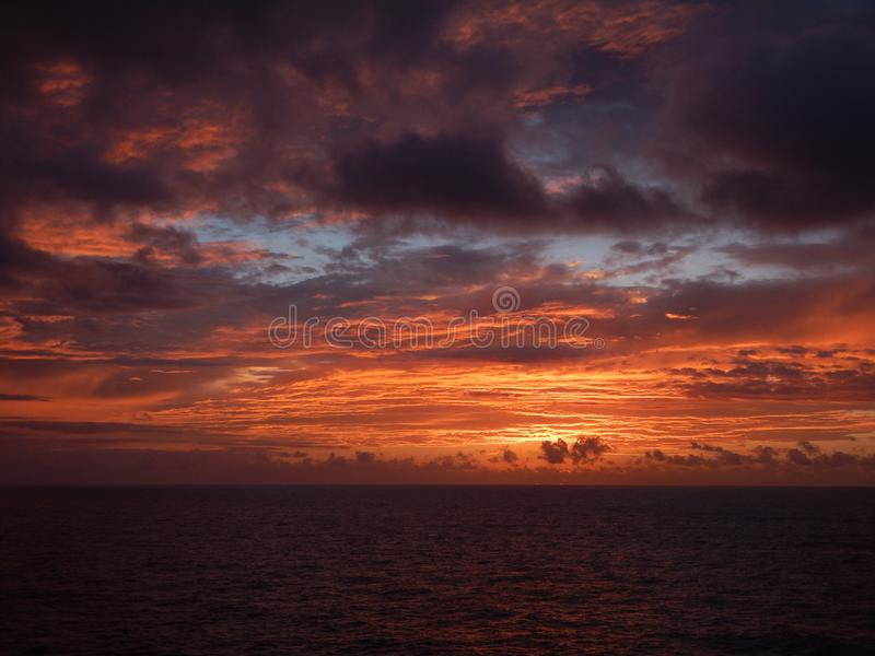 Paradise sunset at open sea. Beautiful sunset at open sea. Clouds seems to be on fire. Picture taken late in the evening stock photography