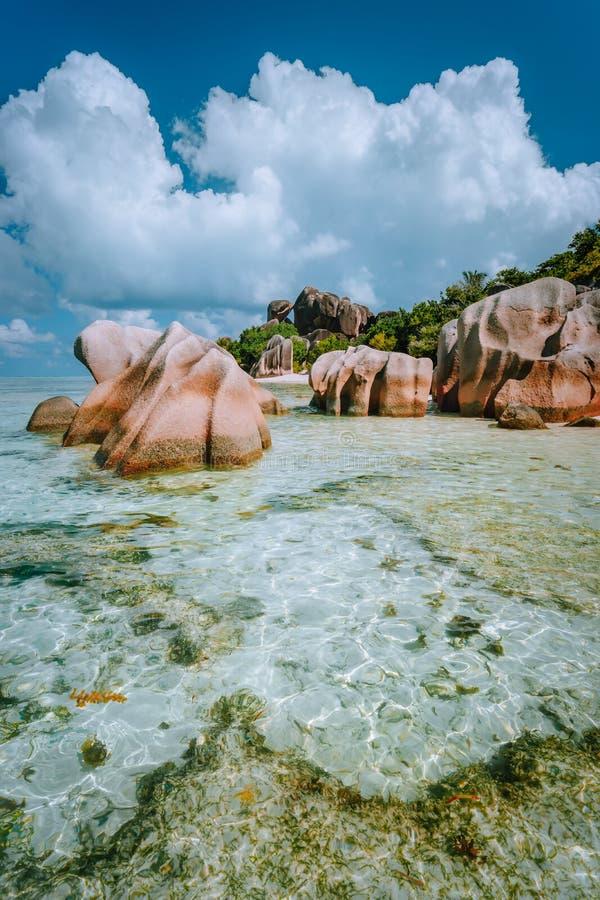 Paradise tropical Beach Anse Source d'Argent con laguna blu poco profonda, massi graniti e nuvole bianche sopra La Digue fotografia stock