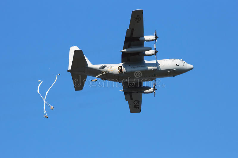 Paradropping. GROESBEEK, NETHERLANDS - SEP 18: Hercules plane drops paratroopers from the 82AD at Market Garden memorial on Sep 18, 2014 in Groesbeek,Netherlan stock image