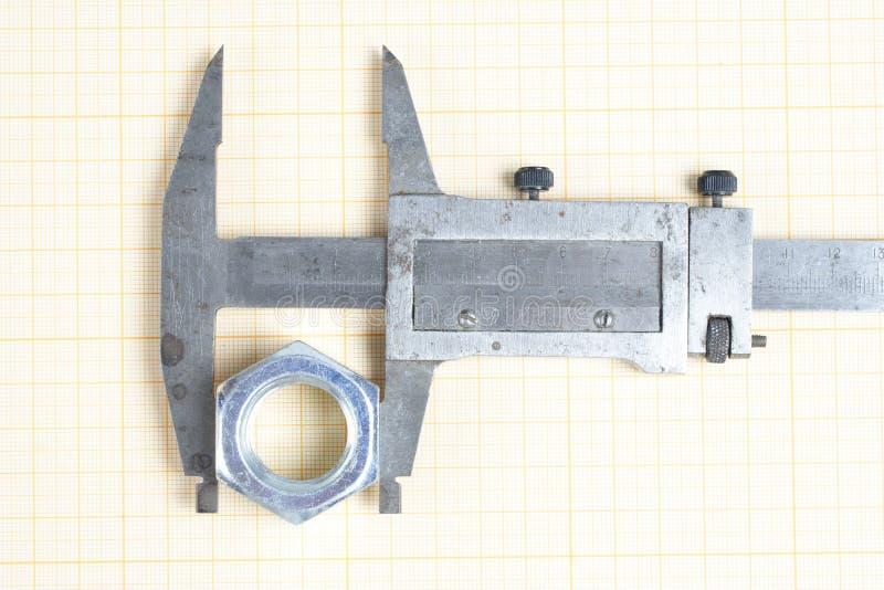 Parafuso, porcas e compasso de calibre no papel de gráfico fotografia de stock royalty free