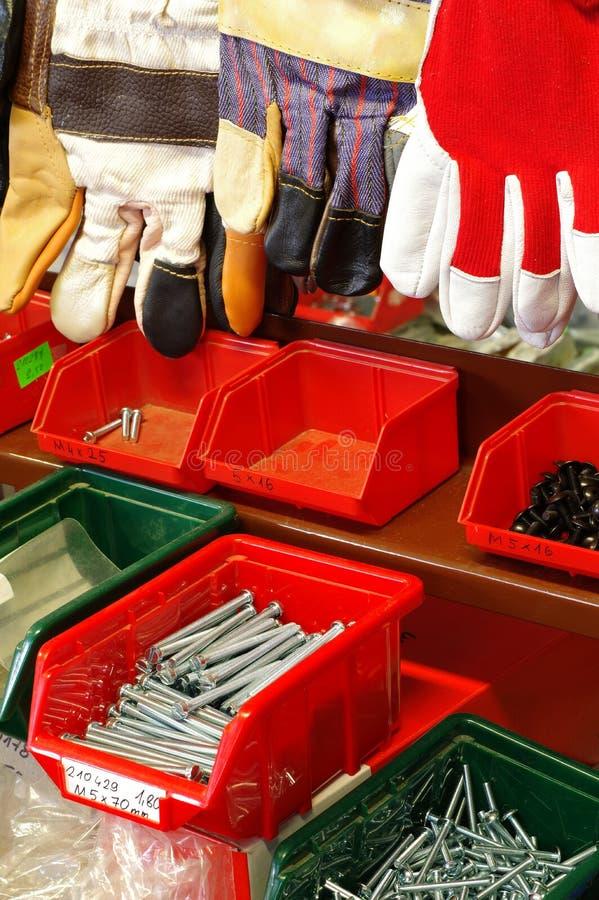 Parafusos da loja em luvas do organizador e do trabalho imagens de stock
